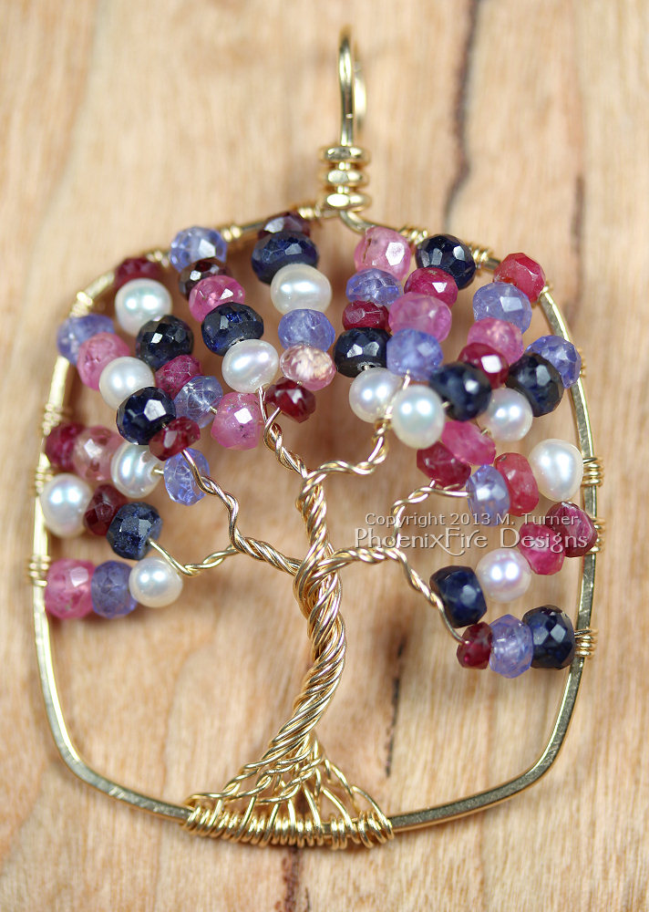 Custom tree of life pendant in SOLID 14k gold and featuring shaded rubies (both red and pink), blue sapphire, tanzanite and freshwater pearls. This was a birthstone tree representing the parents, twins, and pearl for their wedding.