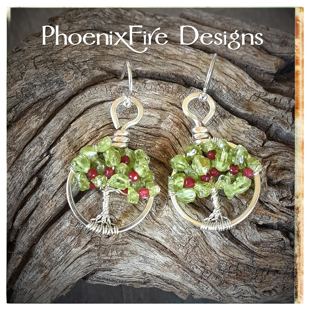 Custom miniature apple tree earrings wire wrapped in silver with peridot leaves and tiny ruby red jade apples in the branches on .925 sterling silver hooks.