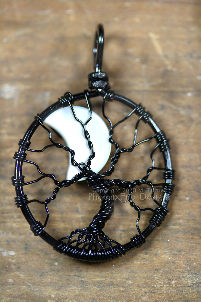 A mother of pearl crescent moon peeks out from behind the black wire branches of this handmade wire wrapped tree of life pendant like a lunar eclipse in the night sky.