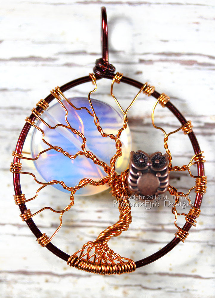 A small copper owl sits in the branches of this two tone, brown and copper Tree of Life pendant featuring an Opalite Rainbow Moonstone Full Moon. Handmade and hand wire wrapped.