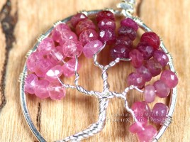 Stunning shaded ombre red, raspberry and pink ruby rondelles in silver wire make up this Tree of Life Pendant featuring July's precious gemstone birthstone.