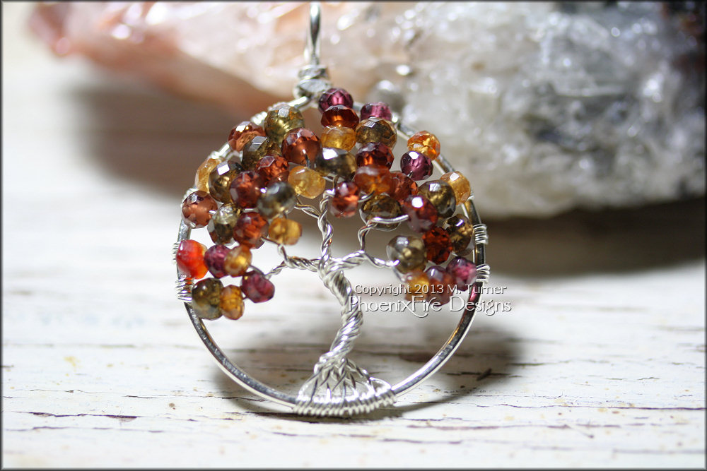 Stunning Tunduru (Tundra) Sapphire in an Autumn range of red, orange, green and plum make up this gorgeous Tree of Life Pendant in non tarnish silver wire.