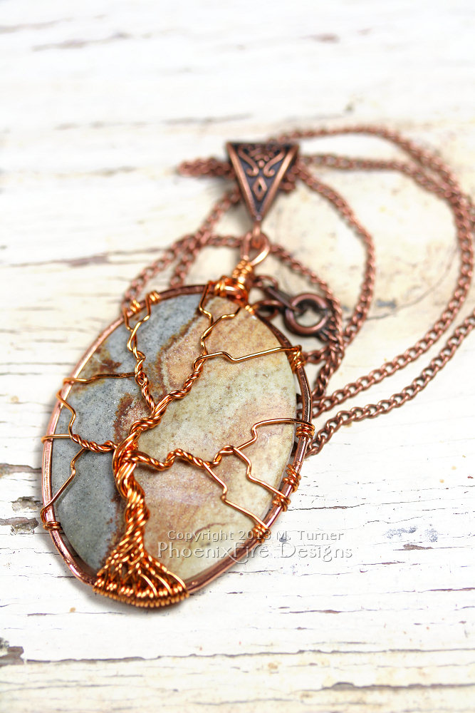 "A multicolor cabochon agate is encircled in copper and a tree of life pendant is wire wrapped on the surface forming this beautiful, natural necklace. On 18"" chain."
