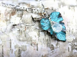 Glowing blue micro-faceted Rainbow Moonstone Briolette is nestled on a verdigris patina brass leaf charm. On a sterling silver plated chain of 18 inches.