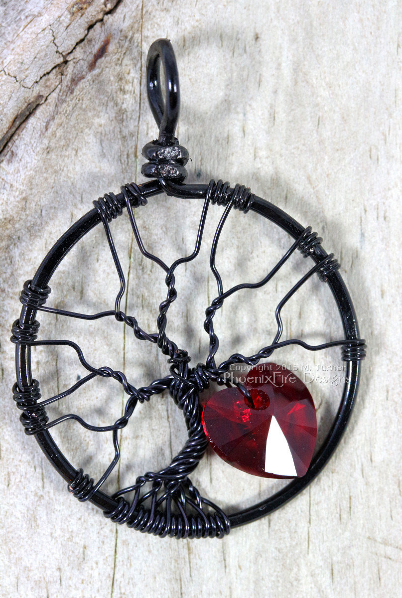 Handmade wire wrapped tree of life pendant black wire with siam red Swarovski crystal heart dangling from the silver wire branches by Phoenix Fire Designs on etsy.