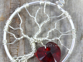 Handmade wire wrapped tree of life pendant with siam red Swarovski crystal heart dangling from the silver wire branches by Phoenix Fire Designs on etsy.