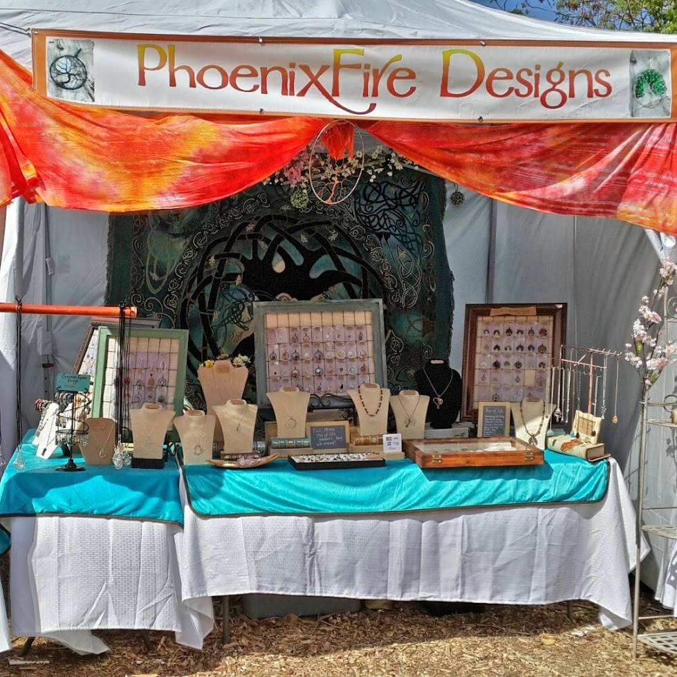 Handcrafted gemstone jewelry and wire wrapped tree of life pendants by PhoenixFire Designs craft show booth display.