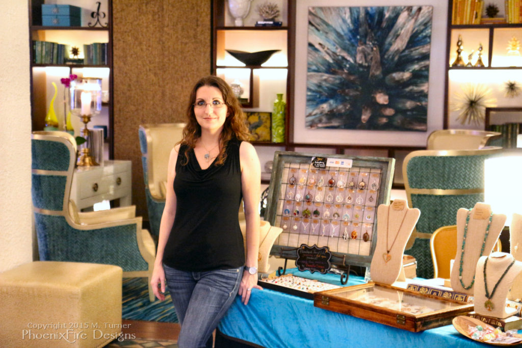 Handmade artisan jewelry maker Miss M. Turner of PhoenixFire Designs in front of her artist showcase display at the Vinoy Renaissance Resort in St Petersburg, Florida. Each handcrafted, wire wrapped gemstone jewelry pendant and necklace is made in our Tampa Bay Studio and available in our etsy shop.
