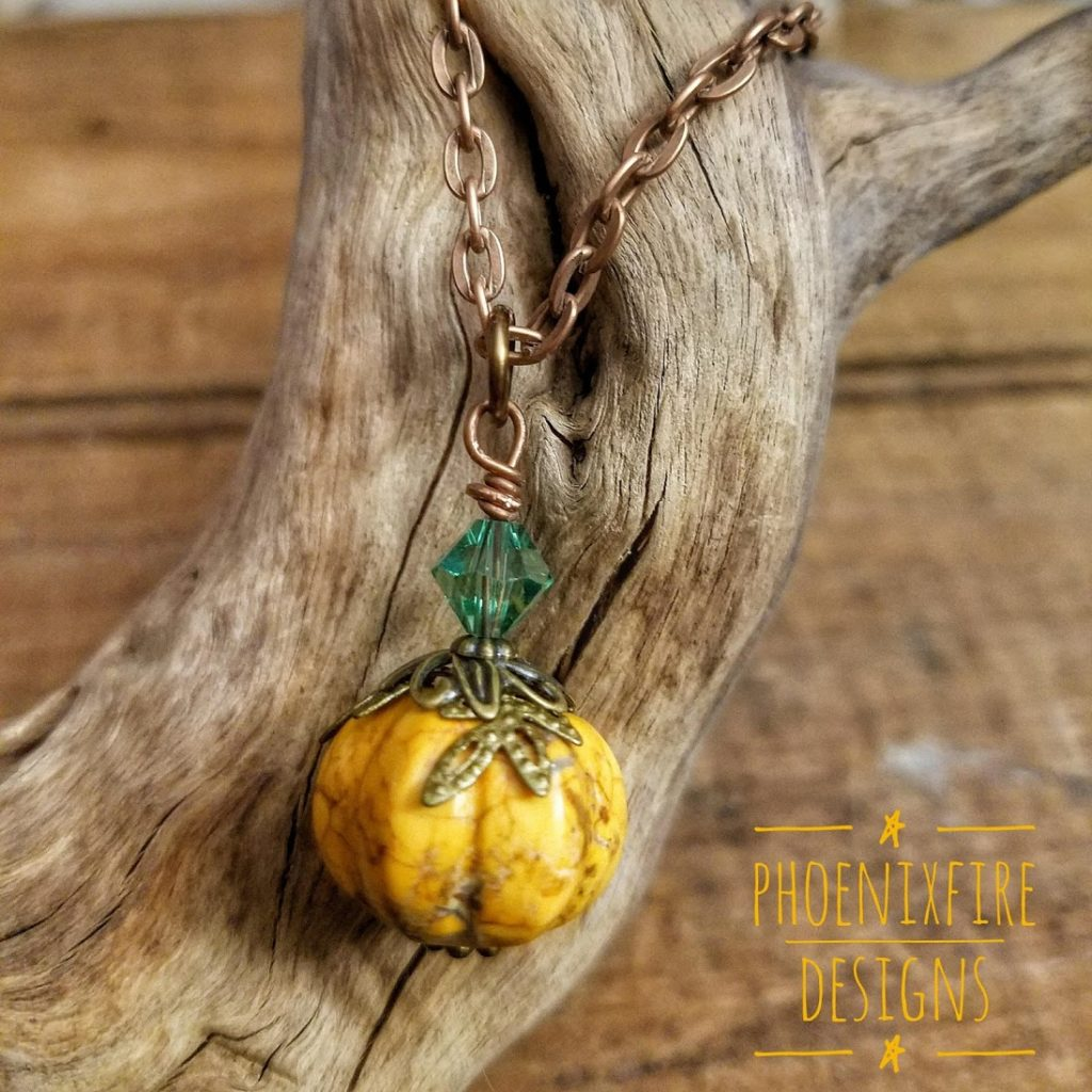 Handmade, orange howlite pumpkin necklace with brass leaf bead caps and Swarovski Crystal accent on antique copper chain. By PhoenixFire Designs