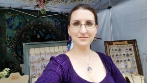 Handmade jewelry designer and wire wrapped tree of life artist, Miss M. Turner of PhoenixFire Designs standing in front of her craft show booth display at the Bay Area Renaissance Festival in Gypsy style costume, long skirts, belly dance skirt, coin belt, peasant blouse, boho style.